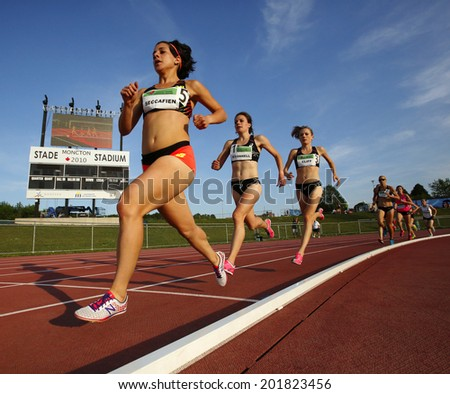 MONCTON, CANADA - June 28: Andrea Seccafien, Jessica O'Connell and Rachel Cliff run in the women's 5000-metre championship at the Canadian Track & Field Championships June 28, 2014 in Moncton, Canada. - stock photo