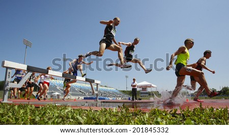 MONCTON, CANADA - June 28: Chris Winter (top), Christopher Dulhanty, Matthew Hughes (9) are some of the steeplechasers at the Canadian Track & Field Championships June 28, 2014 in Moncton, Canada.  - stock photo