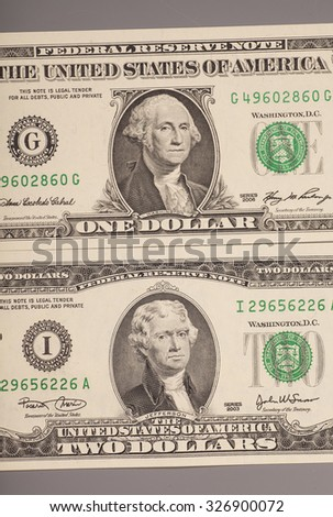 Money American One and Two dollar bills  on gray