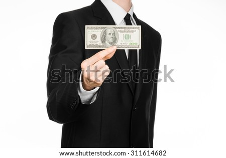 Money and business theme: a man in a black suit holding a bill of 100 dollars and features a hand gesture on an isolated white background in studio