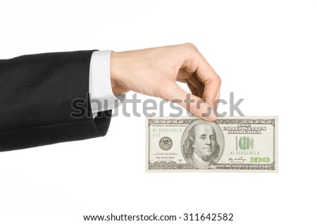 Money and business topic: hand in a black suit holding a banknote of 100 dollars on white isolated background in studio - stock photo