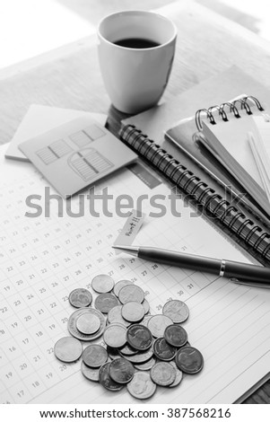 money and calculator on wooden table with black and white color concept - stock photo