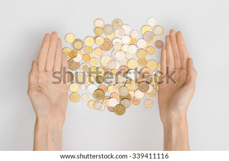 Money and Finance Topic: Money coins and human hand showing gesture on a gray background in studio top view - stock photo