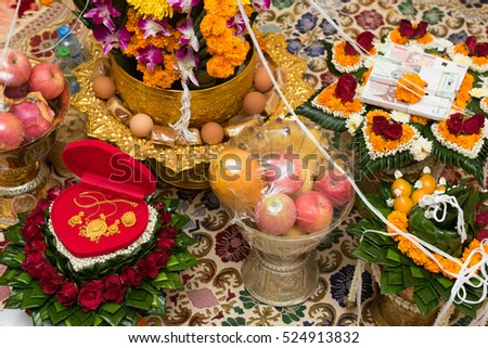 Money and golden jewelry arranged on tray of gift from groom to bride in Lao cultural engagement ceremony.