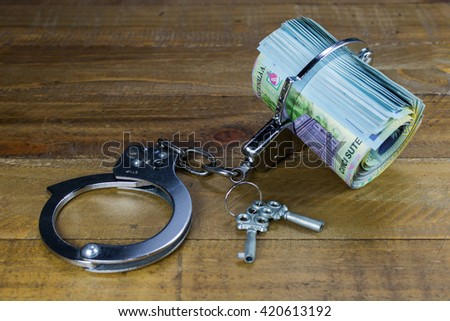 Money and handcuffs. Concept for corruption and bribery - stock photo