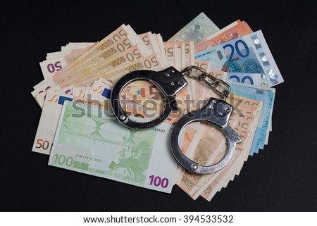 Money and handcuffs. Concept for corruption, fraud, money laundry - stock photo
