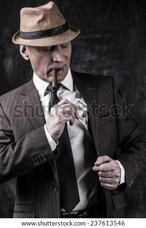 Money and power. Serious senior man in hat and suspenders smoking cigar and hiding money into the pocket while standing against dark background  - stock photo