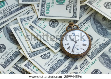 money and time concept - old pocket watch on pile of american dollars