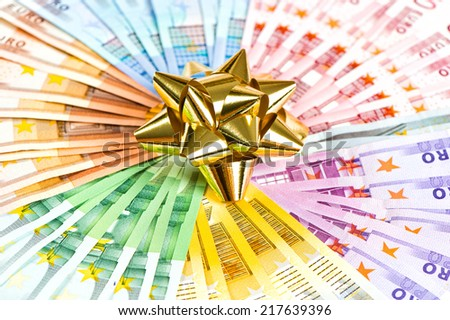 money as a gift. golden ribbon on euro currency banknotes background - stock photo