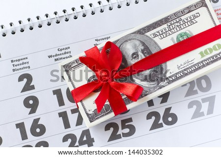 Money as a gift. Roll of money tied up by a red tape on a calendar - stock photo