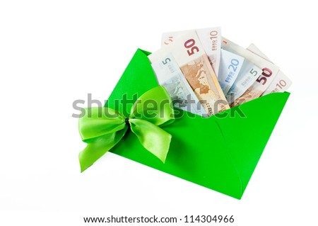 Money as a gift with green bow and green envelope on white background - stock photo