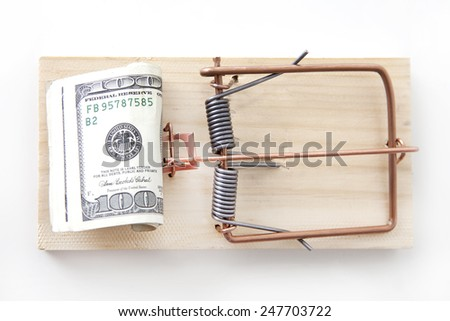 Money as bait in a mouse trap. - stock photo