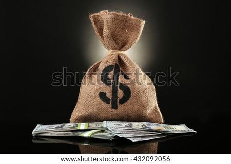 Money bag with dollars on black background - stock photo