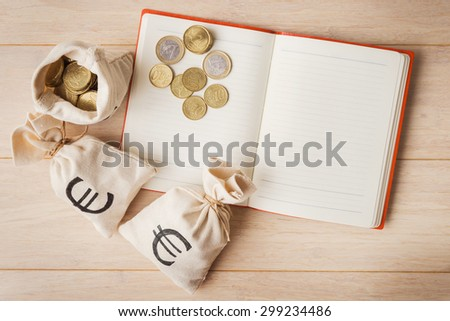 Money bags with euro coins and open notebook on wooden background - stock photo