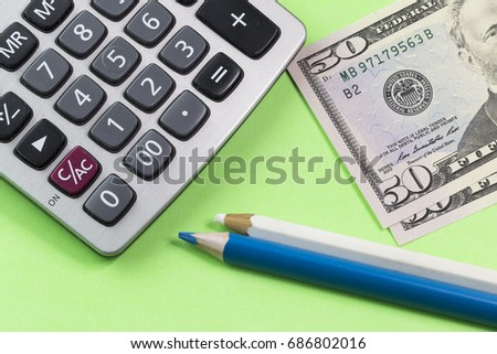 Money, calculator, notepad and pen on green background. Business and finance concept