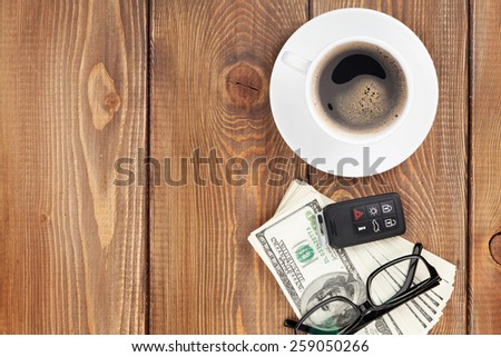 Money cash, glasses, car remote and coffee cup on wooden table with copy space - stock photo