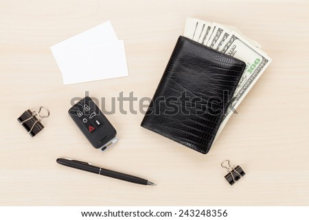 Money cash wallet and car remote key on wooden table. View from above with business cards for copy space - stock photo