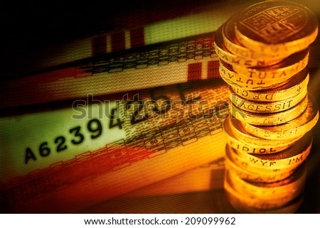 Money concept. A pile of pound coins on top of a selection of bank notes. - stock photo