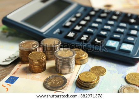 Money concept. Black calculator with banknotes and coins, close up - stock photo