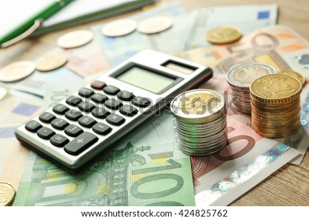 Money concept. Grey calculator with coins and notebook, close up - stock photo