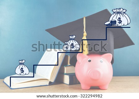 Money concept. Piggy bank with book and grad hat - stock photo