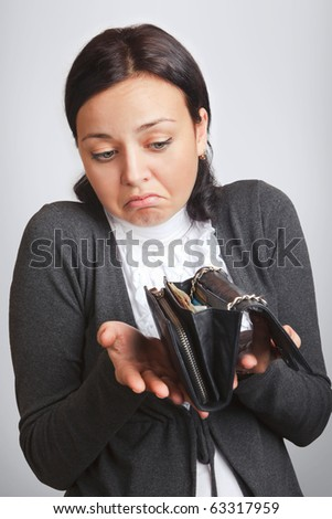 Money contingencies concept. Young confused woman holds wallet in her hands