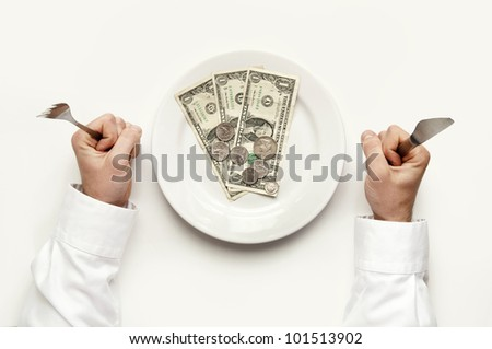 Money diet concept. Man holds fork and knife. Dollar bills and coins on white plate isolated on white from top view. - stock photo