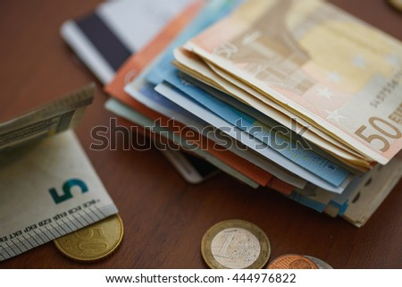 Money euro coins, banknotes and credit cards on wooden background
