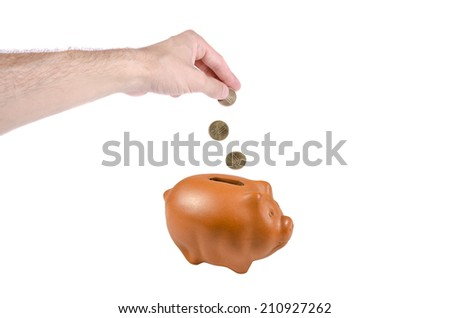 Money falling from a hand intro piggy bank - stock photo
