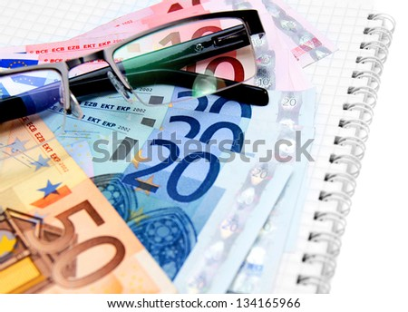 Money, glasses on a notebook.