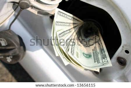 Money going down the gas tank - stock photo