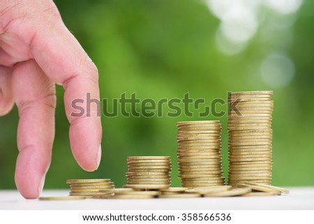 Money Gold coin Steps with green bokeh background ,Business Finance and Money concept,Hope of investor concept,Male hand steps on money coin like stack growing business