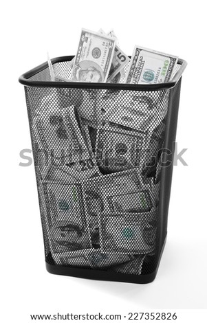 Money in dustbin on grey background