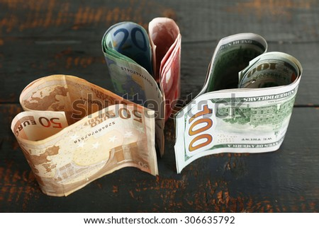 Money in form of hearts on rustic wooden background - stock photo