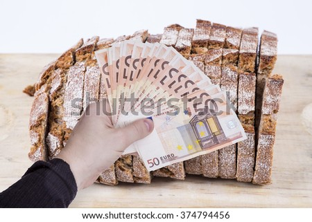 money in hand and artisan bread  - stock photo