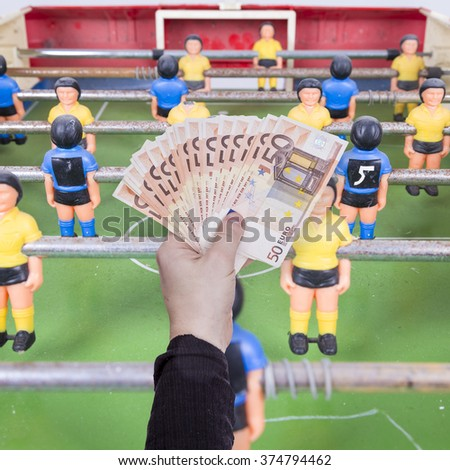 money in hand and playing foosball  - stock photo