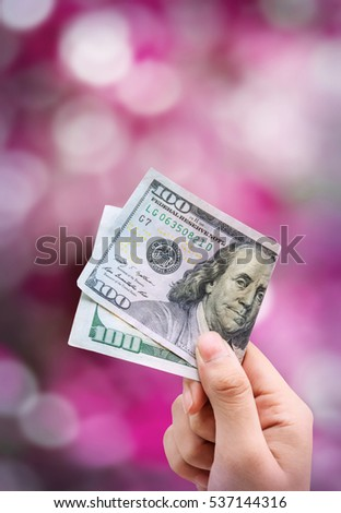 Money in hand, isolated on pink background bokeh