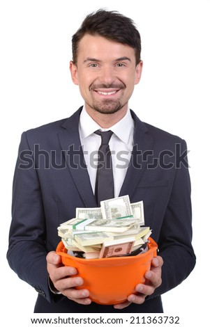 Money in hardhat. Happy young man in formalwear holding hardhat full of money and smiling - stock photo