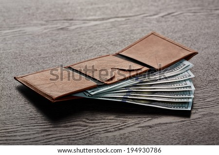 Money in leather wallet - stock photo