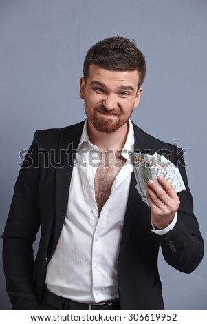 Money in the hands of a cheerful businessman - stock photo