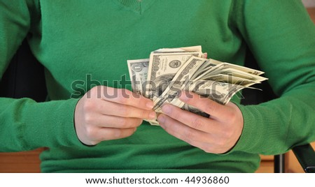 Money in the hands of a young woman - stock photo