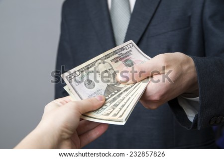 Money in the hands of the people. Convert dollars on gray background - stock photo