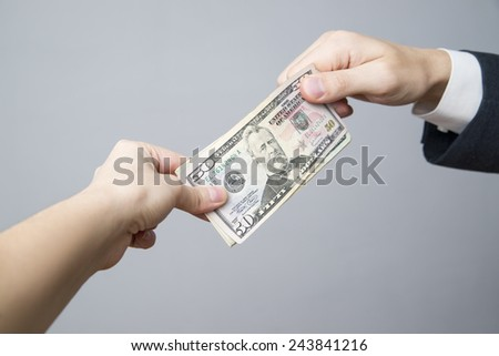 Money in the hands of the people. Convert dollars on gray background