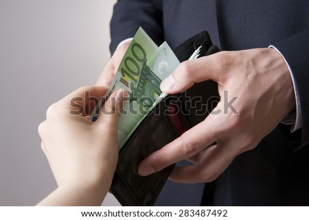 Money in the hands of the people. Convert euro on gray background - stock photo