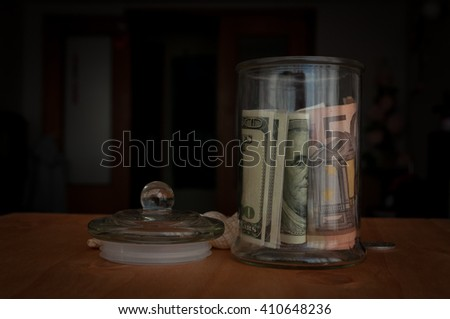 money in the jars on the table, savings for vacation