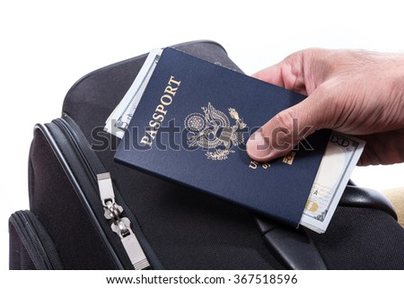 Money in US passport in hand with suitcase, using money for travel around the world concept - stock photo