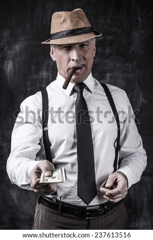 Money is not a problem. Serious senior man in hat and suspenders smoking cigar and stretching out money while standing against dark background  - stock photo