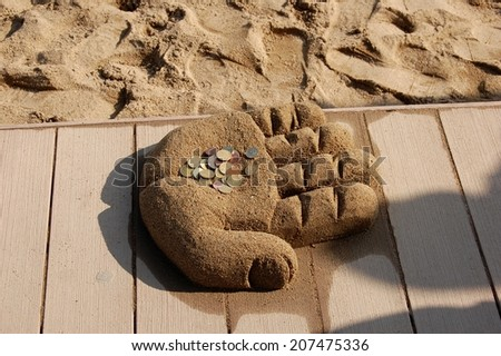 Money lying in a hand of sand   - stock photo