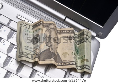 Money on a Laptop Computer as a Conceptual Image for Making Money on the Internet.