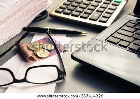 Money on bills with laptop and calculator - stock photo